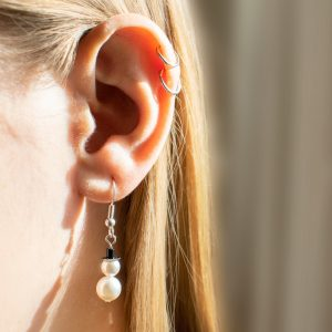 snowmen earrings being worn in ear