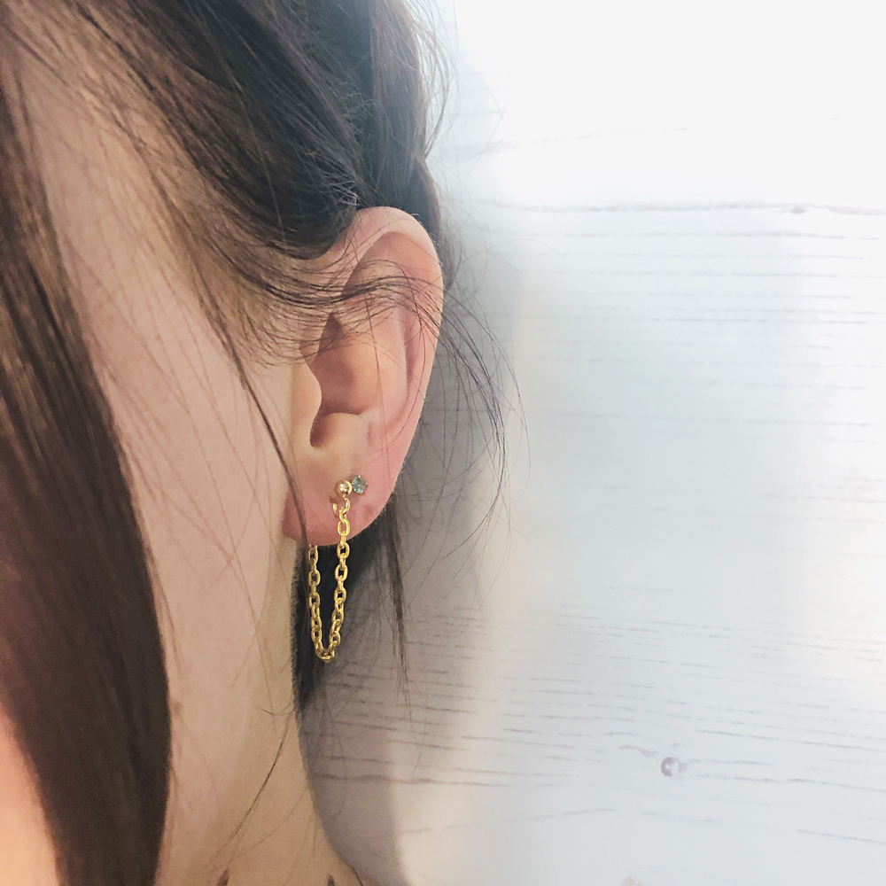 The earring loop hangs from the front to the back of the ear lobe.